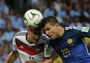 Germany's Miroslav Klose jumps for the ball with Argentina's Sergio Aguero during their 2014 World Cup final at the Maracana stadium in Rio de Janeiro July 13, 2014.  REUTERS/Sergio Moraes (BRAZIL  - Tags: SOCCER SPORT WORLD CUP)   - RTR3YFIQ